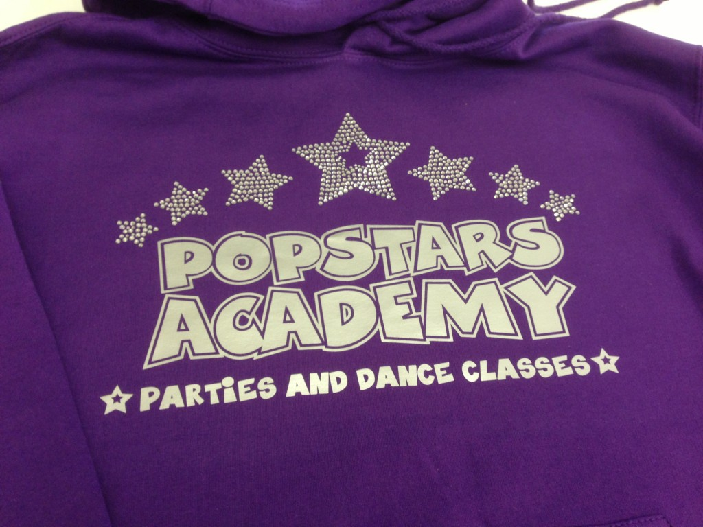 A silver and Crystal Logo on a purple hoodie for Popstars Dance Academy